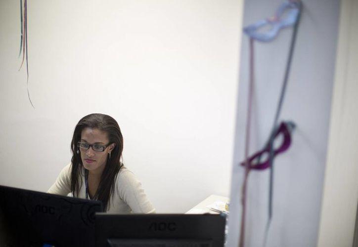 Diana Prado sentada entre los cubículos de sus oficinas en el centro de Río. (Fotos: Agencias)