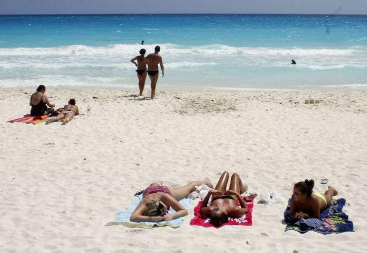 Muchos vacacionistas comparten sus fotografías en las playas, así  como experiencias, a través de teléfonos móviles. (Sergio Orozco/SIPSE)