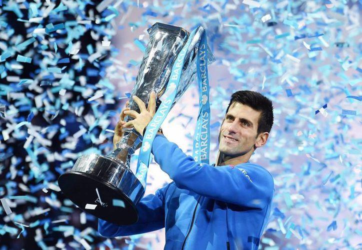 El serbio Novak Djokovic levanta el trofeo que le acredita como campeón del Masters de tenis tras vencer en la final al suizo Roger Federer en Londres. (EFE)