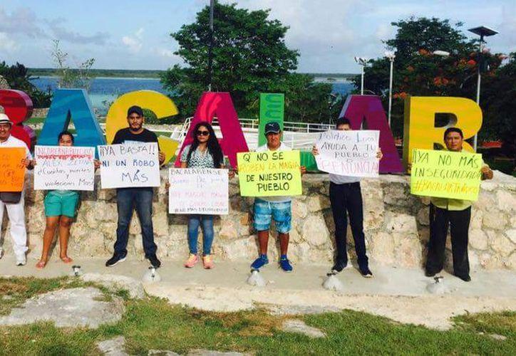 En lugar de marcha, se manifestaron en el parador fotográfico con cartulinas. (Javier Ortiz/SIPSE)