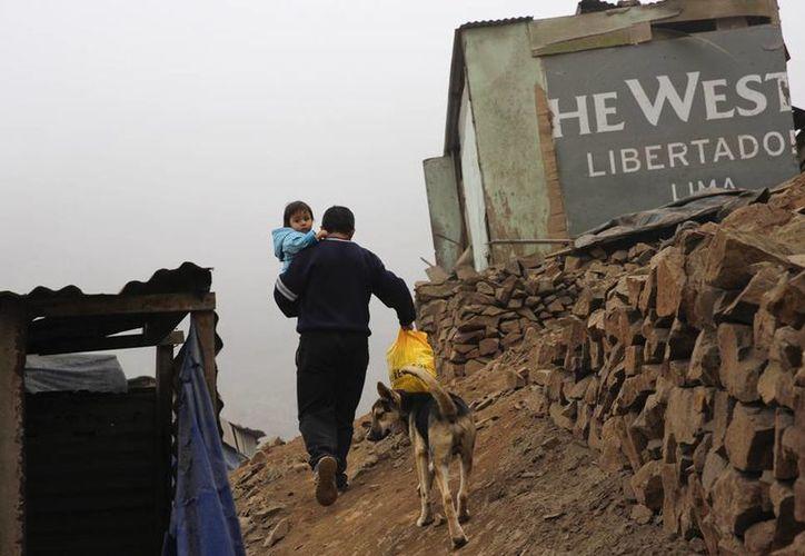 Un residente lleva a su hijo en brazos en el distrito de Villa María del Triunfo, en las afueras de Lima, Perú, una de las tantas barriadas que los turistas deciden visitar. (Agencias)