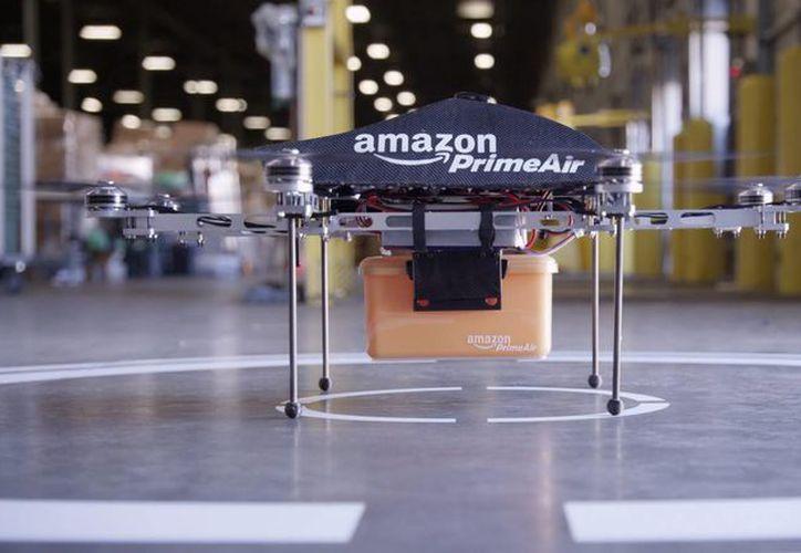 """Imagen cedida por Amazon, que muestra un avión no tripulado o """"dron"""" con una caja de transporte en Seattle, Estados Unidos. (EFE)"""