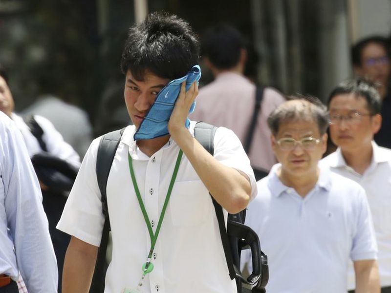 A man wipes the sweat from his face in the scorching heat at a business district in Tokyo. (AP)