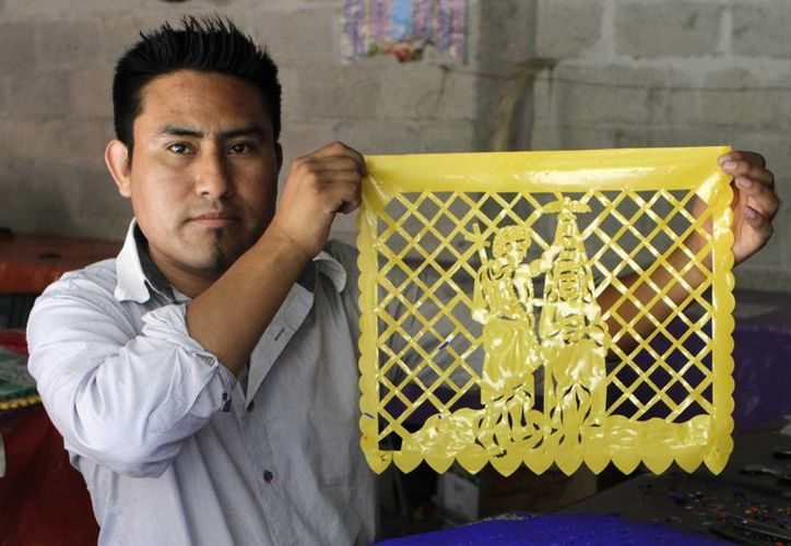 El diseño y corte del papel picado es una labor que implica el trabajo de buena parte de los habitantes de San Salvador Huixcolotla, en Puebla. (Notimex)
