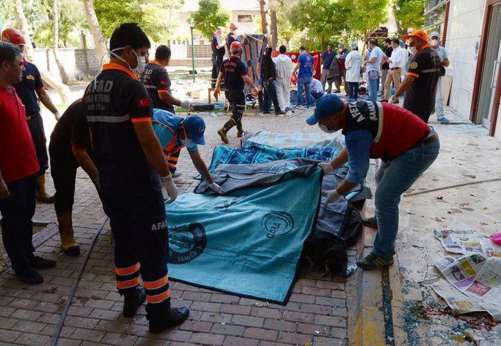Algunos cuerpos de las víctimas son acomodados afuera del Centro Cultural donde ocurrió el mortal atentado, en la ciudad de Suruc, Turquía, el lunes 20 de julio de 2015. (Foto AP)