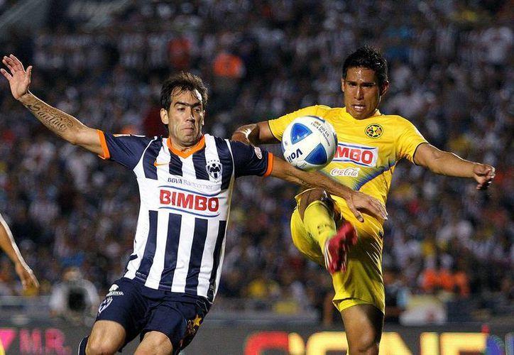 América lució un futbol pobre comparado con partidos anteriores, pero se encontró con un Monterrey aún peor y logró sacarle los 3 puntos. En la foto, Juan Carlos <i>Topo</i> Valenzuela (der.) le gana al balón a César <i>Chelito</i> Delgado