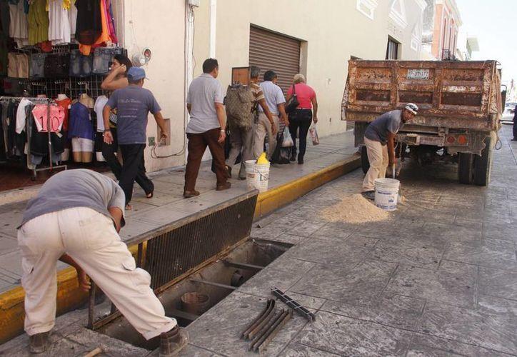 Reparación de rejillas con desperfectos en el Centro Histórico de Mérida. (Juan Carlos Albornoz/SIPSE)
