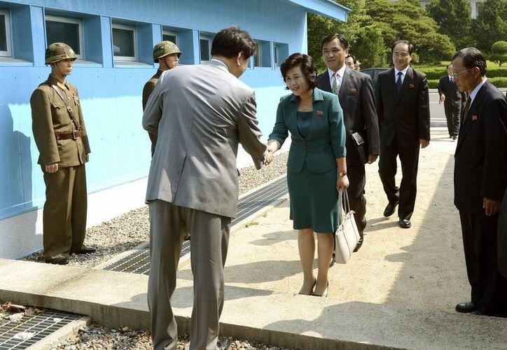 Las delegaciones norcoreana (d) y surcoreana se dan la mano en una línea de demarcación militar para reunirse en Panmunjom, en Paju, al norte de Seúl. (Agencias)