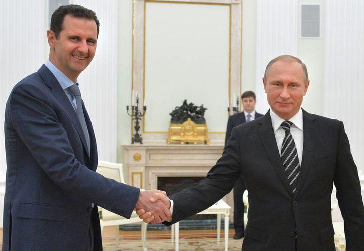 El presidente ruso Vladimir Putin, derecha, estrecha la mano del presidente sirio Bashar Assad en el Kremlin en Moscú. (Agencias)