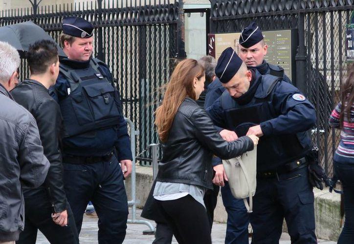 Agentes de la Gendarmería revisan, el jueves 19 de noviembre de 2015, la bolsa a una mujer en el atrio de la catedral de Notre Dame de París, Francia, donde se instaló un control de seguridad para acceder al templo debido a los atentados del pasado viernes. (Notimex)
