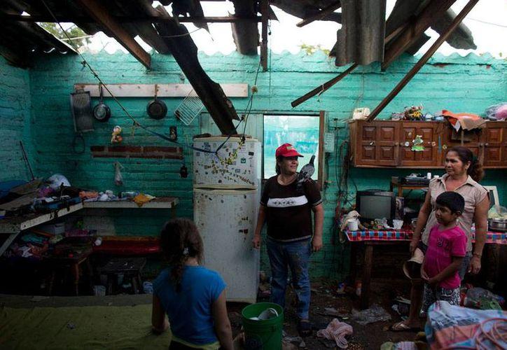 Lo que queda del huracán 'Patricia' se disipará este mismo sábado por la noche, pronosticó el SMN. La imagen es de una casa en La Fortuna, Jalisco, donde causó algunos destrozos. (AP)