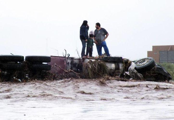 Una familia quedó atrapada al intentar cruzar un camión en un arroyo crecido. (Notimex)