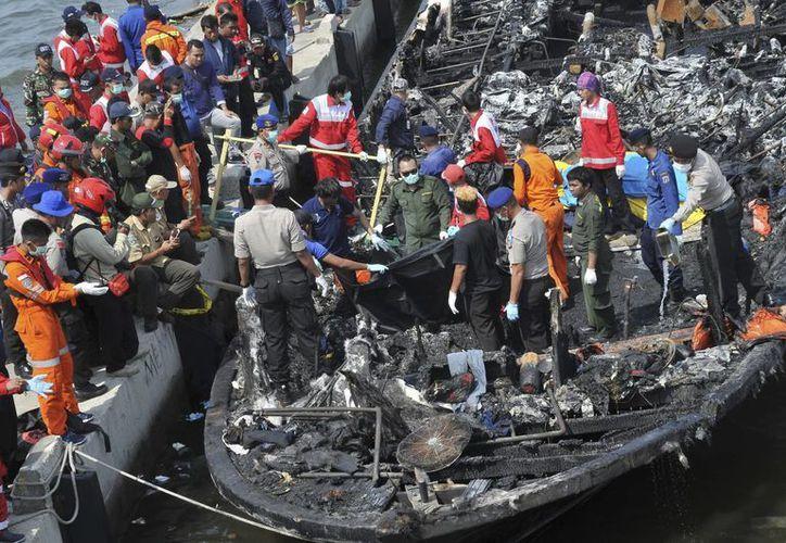 Rescatistas buscan víctimas entre los restos de un transbordador que se incendió ante la costa de Yakarta tras partir del puerto de Muara Angke, en la capital indonesia, el 1 de enero de 2017. El barco trasladaba a más de 230 personas desde la ciudad hasta Tidung, centro turístico en el archipiélago de Kepulauan Seribu, cuando ardió. (AP Foto/Rhana Ananda)