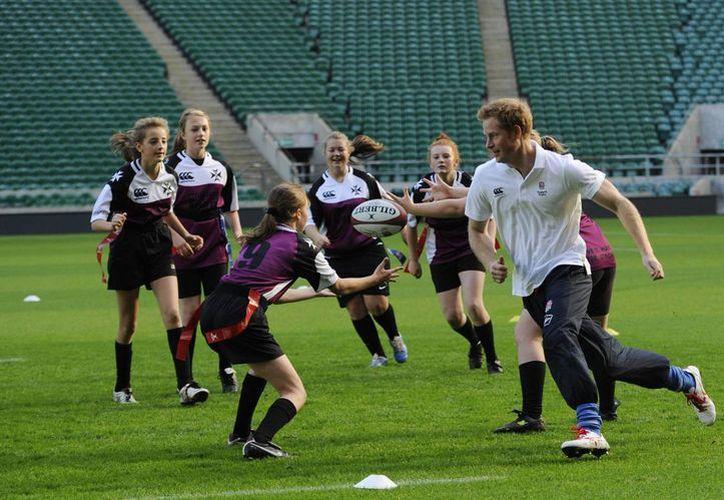 Fotografía tomada el pasado 17 de octubre en la que se registró al príncipe Enrique de Inglaterra (d) al participar en un entrenamiento de rugby con estudiantes de secundaria, en el estadio Twickenham en Londres. (EFE/Archivo)