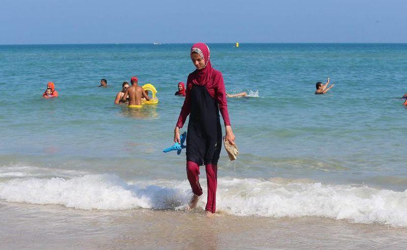 Una mujer camina con un burkini en la playa de Bizerte, en Túnez. Esta prenda ha creado polémica en países como Francia. (EFE/Archivo)