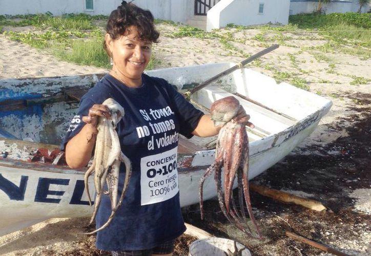 Imagen de una mujer con dos pulpos que capturó a la orilla de la playa. (Milenio Novedades)