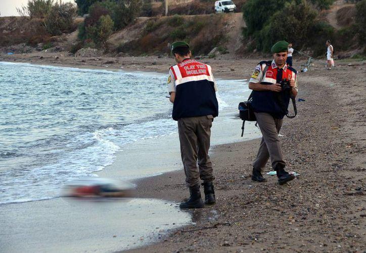Esta fotografía tomada en una playa turca refleja la gravedad de la crisis migratoria más dura que ha vivido Europa desde la Segunda Guerra Mundial. La imagen del cadáver fue difuminada por discreción. (AP)