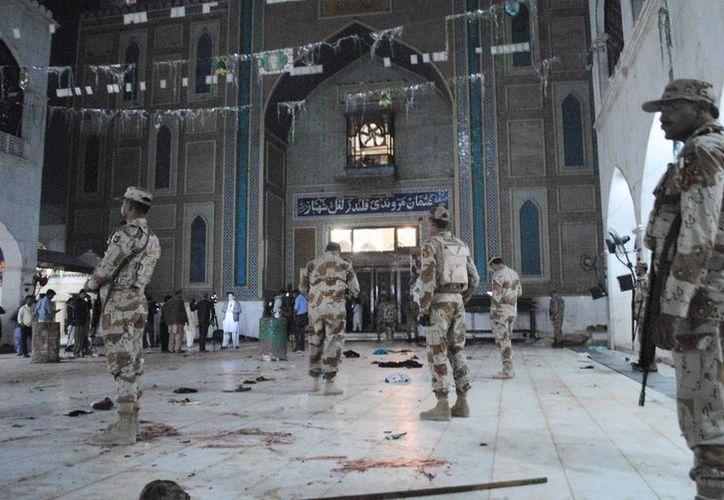 Soldados paramilitares paquistaníes están alerta después de un ataque suicida mortal en el santuario de Sufi Lal Shahbaz Qalandar en Sehwan, Pakistán, este jueves. Un bombardero suicida del estado islámico atacó a fieles del lugar y dejó decenas de muertos y cientos de heridos, dijeron las autoridades. (AP Photo / Pervez Masih)