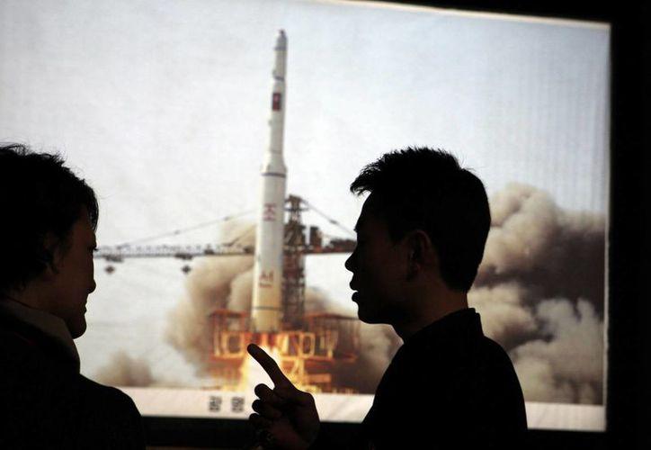 La Agencia espacial desarrolló el satélite Kwangmyongsong-4 para sondear la tierra y logró ponerlo en órbita. Imagen de un par de personas y de fondo una fotografía de la representación del lanzamiento de un cohete. (Foto AP / Ng Han Guan, archivo)