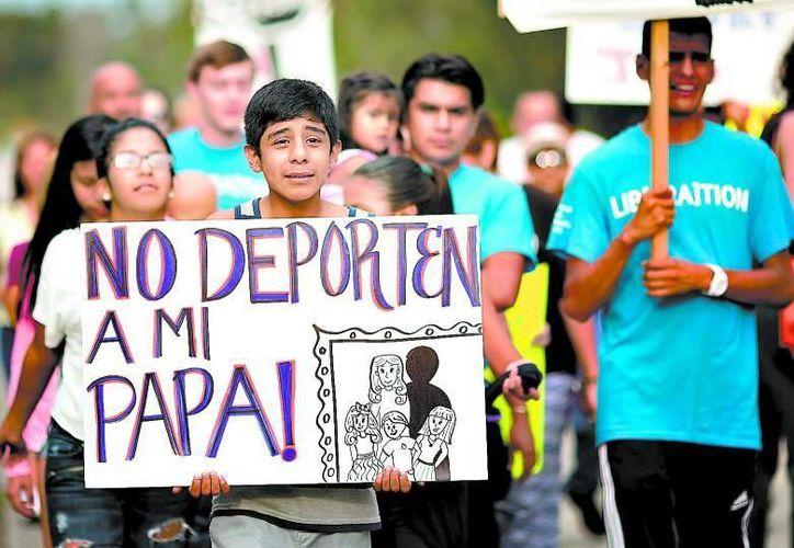 Julio Pérez y otros miembros de Coaliciones Inmigratorias de la Florida frente al Centro de Detención Krome de Miami, para pedir que no deporten al padre del menor. (AP Foto/J Pat Carter)