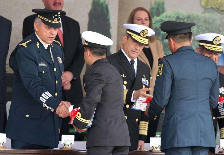 Tradicionalmente, los ascensos a militares son conferidos el 20 de Noviembre, en el marco de los festejos del aniversario del inicio de la Revolución Mexicana. En la imagen, los secretarios de Defensa y de Marina entregan los despachos a personal ascendido. (Archivo/Notimex)