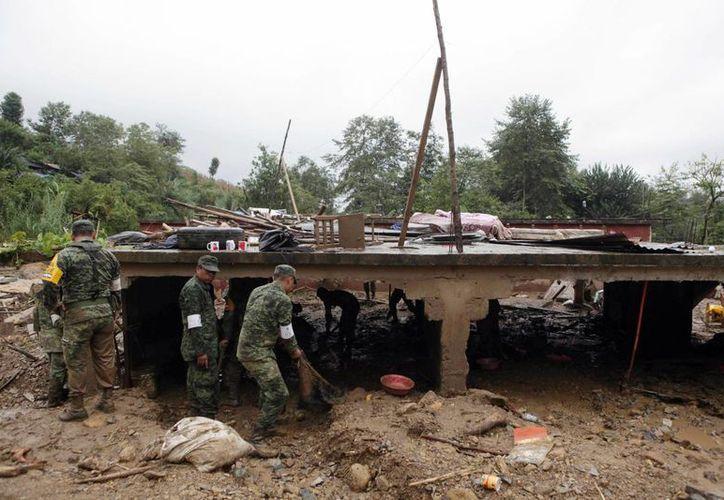 Soldados mexicanos apoyan en la limpieza de la zona, por el deslizamiento de tierra en Xaltepec, zona montañosa al norte de Puebla. (Foto AP/Pablo Spencer)