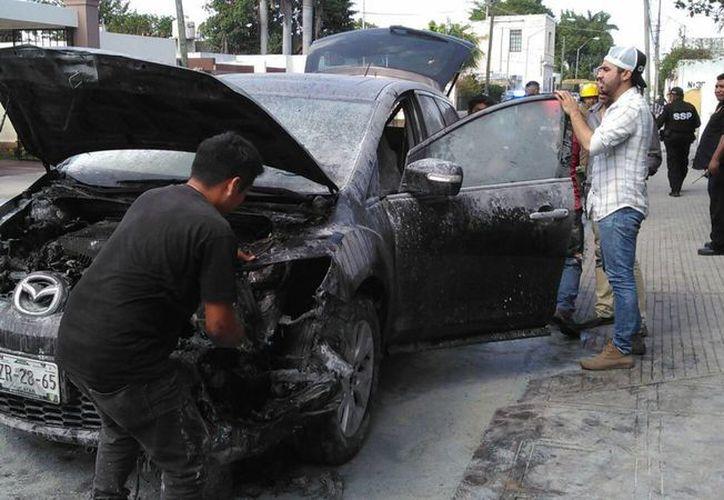 El frente del Mazda CX6 quedó chamuscado por el fuego hoy en la calle 62 por 33 C y 35 de esta ciudad. (Jorge Acosta/SIPSE)