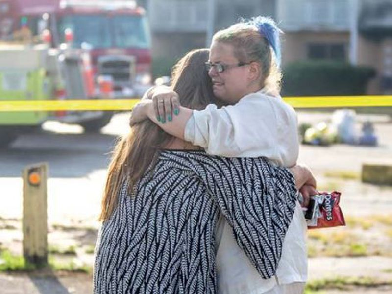 Hotel residents Cassundra Clements, left, and Sarah Sanders comfort one another after a fire at the Cosmo Extended Stay Motel in Sodus Township, Mich. (AP)