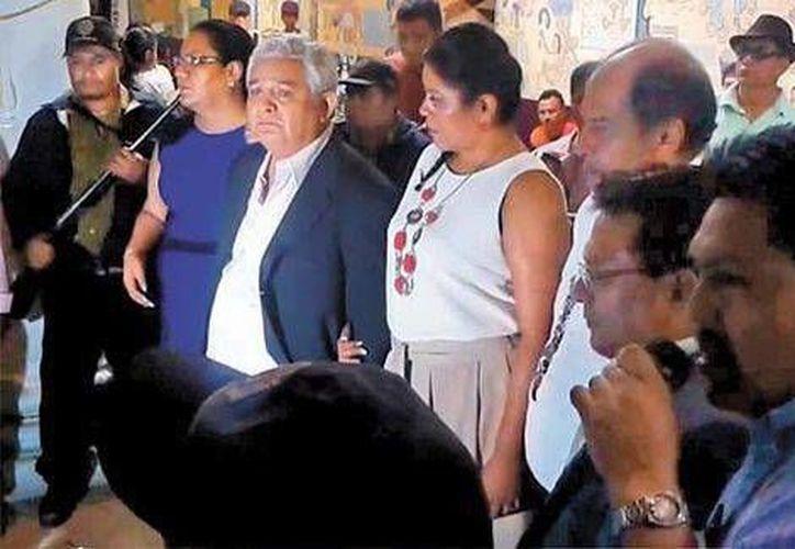 En la imagen se aprecia a un sujeto armado custodiando a los periodistas durante el juicio popular. (Milenio)