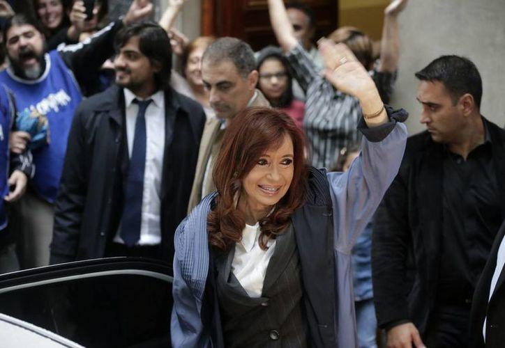 La expresidenta argentina Cristina Fernández saluda a sus partidarios afuera de su apartamento antes de dirigirse a los tribunales en Buenos Aires. (Agencias)