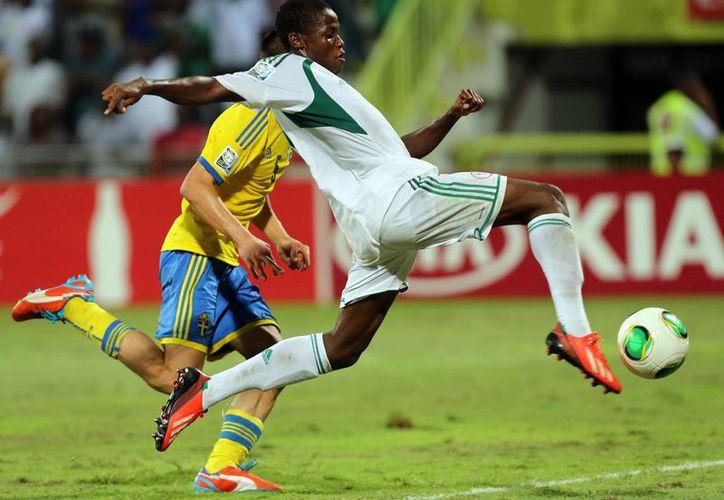 El nigeriano Chidera Ezeh se lleva por velocidad a un jugador sueco en la semifinal disputada en el estadio Rashid de Abu Dhabi. (Agencias)