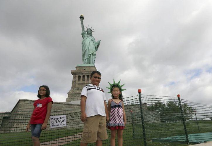 Niños posan desde la base de la Estatua de la Libertad. (Agencias)