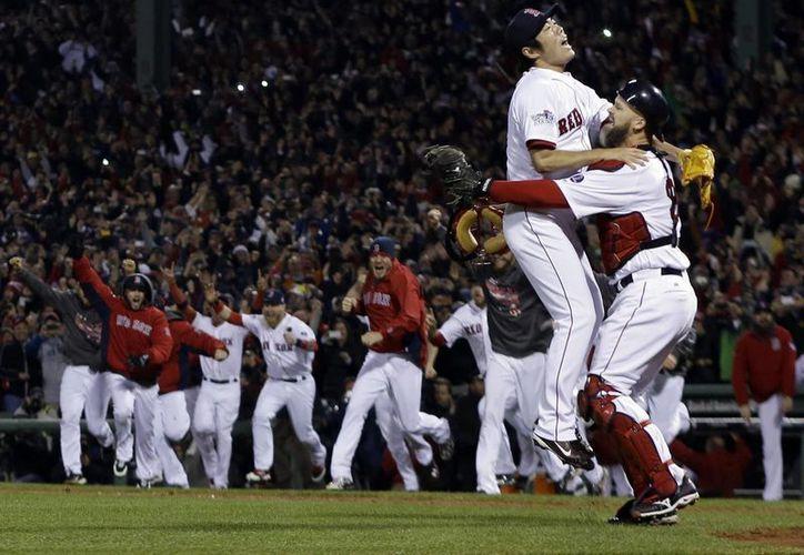Tras el último out el pitcher Koji Uehara festeja con el catcher David Ross la obtención del título. (Agencias)