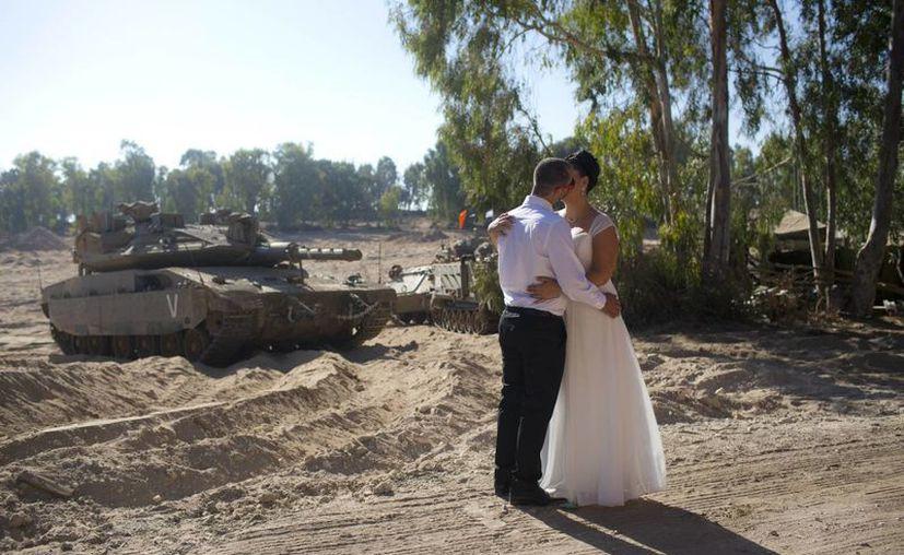 Una pareja de recién casados aprovecharon el fin de la tensión en la Franja de Gaza para tomarse una fotografía del recuerdo con un tanque de guerra israelí como fondo. (AP)