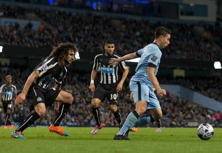 El francés Samir Nasri logra llevarse el balón ante el acoso de dos rivales del Newcastle, que venció 2-0 a Manchester City dentro de la Copa de la Liga inglesa. (Foto: AP)
