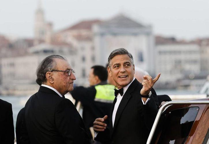 El actor George Clooney habla con Ramzi Alamuddin, padre de su prometida Amal Alamuddin, en un bote que los llevaría al hotel de Venecia donde se casaron. (Foto AP/Luca Bruno)