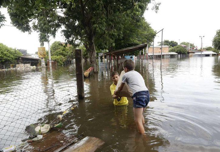 Marino Gomez entrega un saco de comida a su hermano Pablo en una zona inundada del vecindario Bañado Norte, en Asunción, Paraguay, este domingo 27 de diciembre. Las peores inundaciones de las últimas décadas, causadas por las lluvias, han forzado la evacuación de más de 140 mil personas en Paraguay, Argentina, Uruguay y Brasil. (Foto AP/Jorge Saenz)