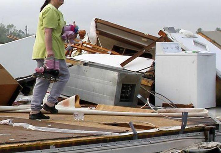 Teresa Ingram recoge algunas de las cosas de su hija después de que un tornado destruyó el centro para casas rodantes Billy Barbs en Alabama. (Agencias)