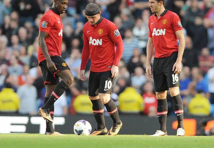Los jugadores del Manchester United Michael Carrick (d) , Wayne Rooney (c) y Danny Welbeck (I) reacciona tras recibir un gol del Manchester City. (EFE)