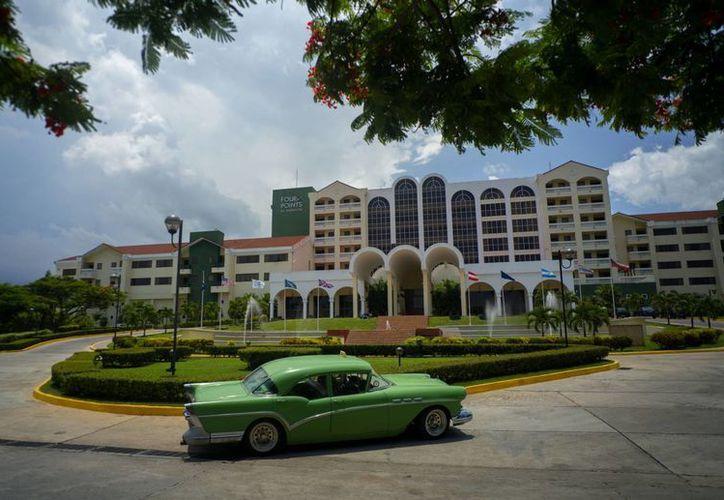 Un auto vintage pasa por delante del hotel Four Points by Sheraton en La Habana, Cuba. El gigante hotelero estadounidense comenzó a gestionar este inmueble propiedad del gobierno cubano. (AP/Ramon Espinosa)
