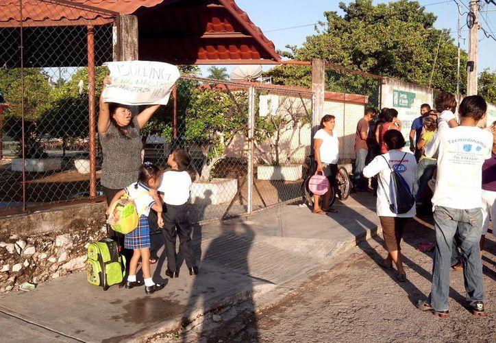 """Una madre de familia llevó un cartel a las puertas de la escuela que decía: """"Bullyng de los maestros con nuestros hijos"""" (sic). (Milenio Novedades)"""