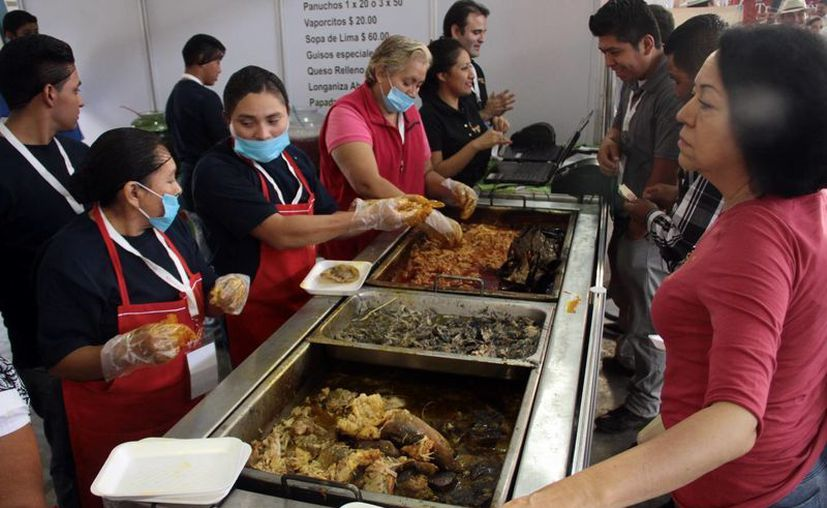 La comida tradicional es uno de los atractivos del Estado para los turistas. Imagen de un grupo de comensales mientras esperan sus tacos o tortas de guisos yucatecos. (Milenio Novedades)