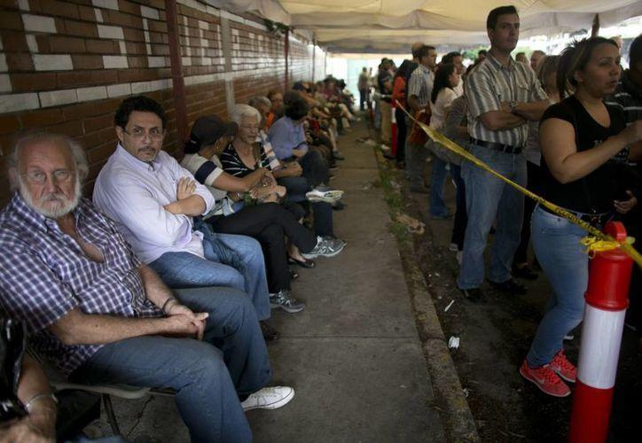 Ciudadanos venezolanos hacen fila a las afueras de una escuela en Caracas a la espera de participar en la validación de firmas que llevará al referendo contra el presidente Nicolás Maduro. (AP)