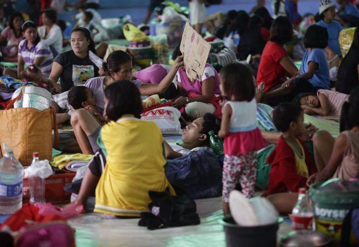 Imagen de residentes evacuados por el tifón Hagupit en un albergue en los suburbios de la ciudad de Quezon al noreste de Manila, Filipinas. (Agencias)