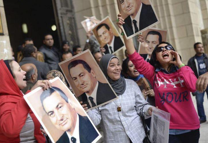 Simpatizantes del expresidente egipcio Hosni Mubarak sostienen fotografías suyas durante una concentración de apoyo tras conocer la decisión del Tribunal de Casación en El Cairo, Egipto. (EFE)