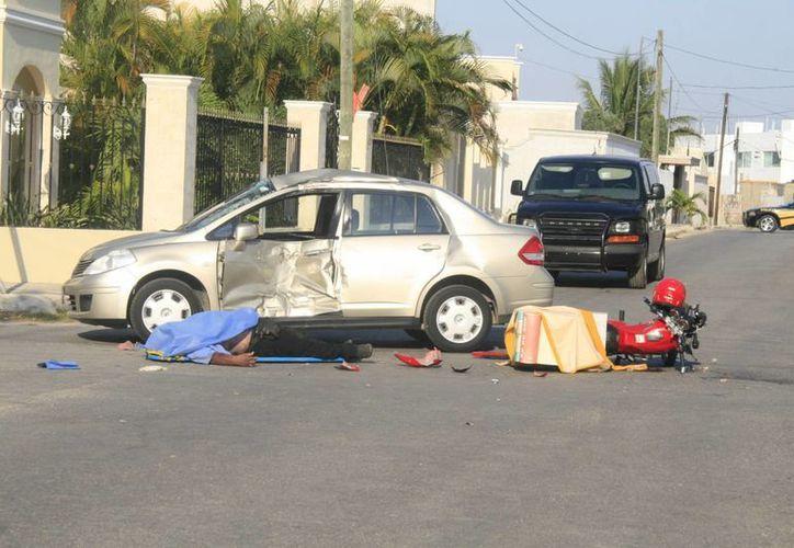 El motoclcista quedó tirado junto al coche y su vehículo ligero. (Jorge Sosa/SIPSE)