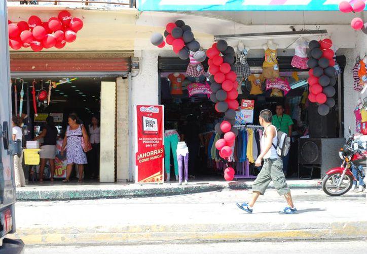 """Los grandes anuncios """"rojiblancos"""" de El Buen Fin logran visualizarse en las tiendas ubicadas en el primer cuadro de la ciudad. (Tomás Álvarez/SIPSE)"""