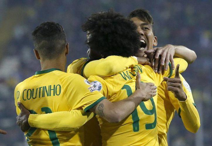 El centrocampista brasileño Roberto Firmino (d) celebra, con sus compañeros Willian y Coutinho, el segundo gol para Brasil, durante el partido del grupo C de la Copa América de Chile 2015. (EFE)