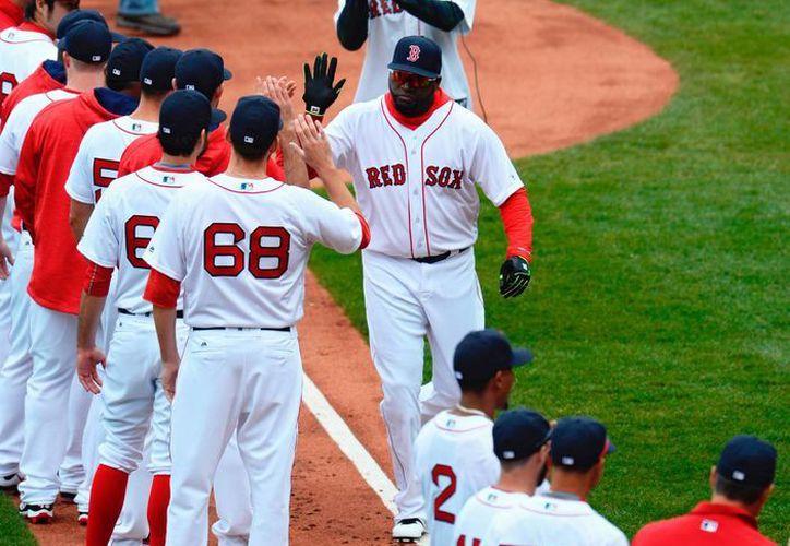 Big Papi saluda a sus compañeros de Medias Rojas de Boston. Un batazo que dio durante una práctica llamó más la atención que muchos que ha logrado en partidos oficiales. (EFE)