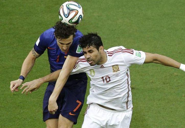 Diego Costa (d) no metió gol, pero participó del juego de España en la primera parte del partido contra Holanda y forzó el penal que transformó Xabi Alonso en la única anotación de la Roja. (AP)